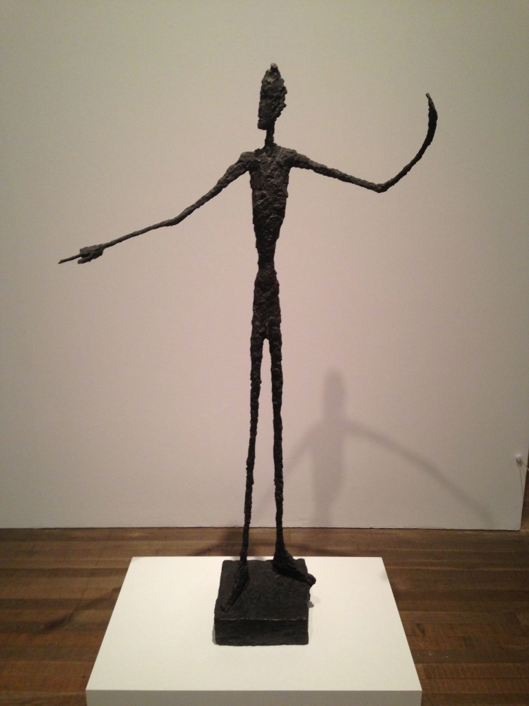 This beautiful re-imagining of the human form by Alberto Giacometti shows a man standing on an iron square, mounted on a bigger, woooden square